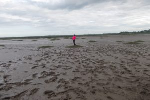 Young Person in a landscape of mud, enjoying the group outing with their befriender.
